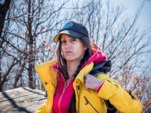 Wanderer der erwachsenen Frau, der gelbe Jacke und schwarzen den Sporthut an setzt ihren Rucksack trägt Lizenzfreie Stockfotos