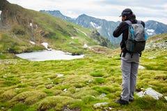 Wanderer, der Fotos der Landschaft macht Stockbild