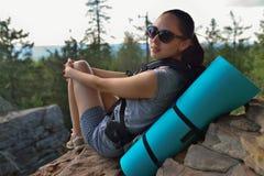 Wanderer der jungen Frau, der auf einer Klippe sitzt und zur Kamera schaut stockbilder
