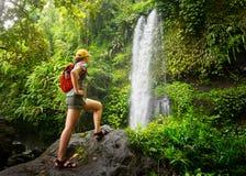 Wanderer der jungen Frau, der den Wasserfall in den Dschungeln betrachtet lizenzfreies stockbild
