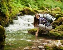 Wanderer der jungen Frau durch den Fluss Lizenzfreie Stockbilder