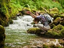 Wanderer der jungen Frau durch den Fluss Stockfotos