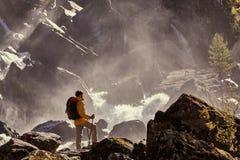 Wanderer, der mit dem Rucksack betrachtet Wasserfall wandert Stockfoto
