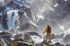Wanderer, der mit dem Rucksack betrachtet Wasserfall wandert Stockbild