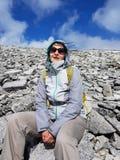 Wanderer, der mitten in dem felsigen Berghang stillsteht stockbilder