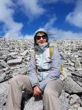 Wanderer, der mitten in dem felsigen Berghang stillsteht lizenzfreies stockfoto