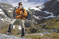 Wanderer, der Mobiltelefon mit Spazierstock in den Bergen verwendet Lizenzfreie Stockfotos
