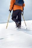 Wanderer, der oben auf eine schneebedeckte Steigung geht Stockfotografie