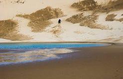 Wanderer, der oben eine Sanddüne klettert stockfoto