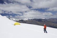 Wanderer, der in Richtung zum Zelt in Snowy-Bergen geht Lizenzfreie Stockfotos