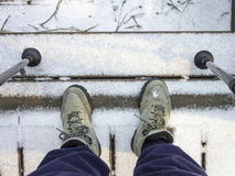 Wanderer, der unten Stiefeln auf Treppe im Schnee mit Pfosten betrachtet Lizenzfreie Stockbilder