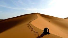Wanderer, der zur Spitze der großen Sanddüne im roten Dünenmeer des Ergs Chebbi, Marokko klettert Lizenzfreie Stockfotografie