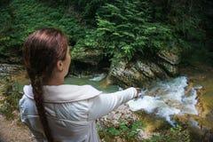 Wanderer des jungen Mädchens steht über Gebirgsschluchtschlucht mit Fluss Stockfoto