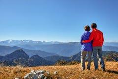 Wanderer, die die Ansicht genießend betrachtet Berglandschaft wandern Stockbilder