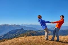 Wanderer, die die Ansicht genießend betrachtet Berglandschaft wandern Stockfotos