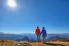 Wanderer, die die Ansicht genießend betrachtet Berglandschaft wandern Lizenzfreie Stockfotos