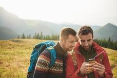 Wanderer, die ein Mobiltelefon während heraus Trekking in der Wildnis verwenden lizenzfreie stockfotos