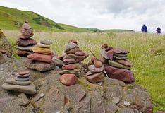 Wanderer, die einige Steinhaufen in einer hügeligen Landschaft führen Lizenzfreie Stockfotos