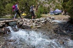 Wanderer, die Fluss kreuzen lizenzfreie stockbilder