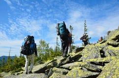 Wanderer, die oben den Berg steigen. Lizenzfreies Stockbild