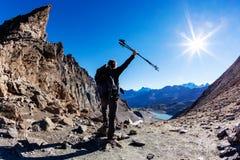 Wanderer erreicht einen hohen Gebirgspass; er zeigt seine Freude an den offenen Armen lizenzfreie stockbilder