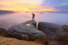 Wanderer am Felsenende über Tal Bemannen Sie Uhr über nebelhaftem und herbstlichem Morgental zum hellen Morgen Sun Lizenzfreie Stockbilder