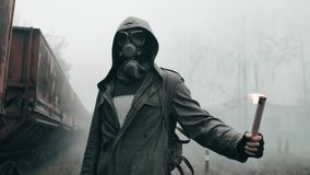 Wanderer in gas mask at abandoned train station holding signal fire in hand