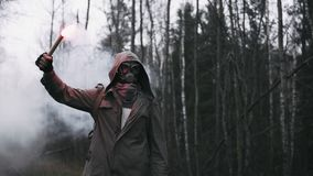 Wanderer in gas mask standing on railway in forest holding signal fire in hand