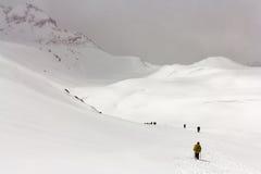 Wanderer gehen auf den Schnee in den Bergen Stockbild