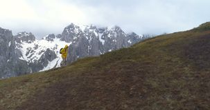Wanderer geht auf einen Hügel vor dem hintergrund der Schnee-mit einer Kappe bedeckten Berge stock footage
