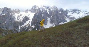 Wanderer geht auf einen Hügel vor dem hintergrund der Schnee-mit einer Kappe bedeckten Berge stock video footage