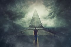 Wanderer guy confident walking a surreal road and found a magic stairway going up to a door in the sky royalty free stock photo