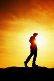 Wanderer im roten Sweatshirt mit roter Kappe auf felsiger Spitze Mann, der über Tal zu Sun aufpasst Schöner Moment Stockbilder