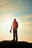 Wanderer im roten Sweatshirt mit roter Kappe auf felsiger Spitze Mann, der über Tal zu Sun aufpasst Schöner Moment das Wunder der Stockfoto