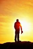 Wanderer im roten Sweatshirt mit roter Kappe auf felsiger Spitze Mann, der über Tal zu Sun aufpasst Schöner Moment das Wunder der Stockbild