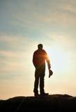 Wanderer im roten Sweatshirt mit roter Kappe auf felsiger Spitze Mann, der über Tal zu Sun aufpasst Schöner Moment das Wunder der Lizenzfreie Stockfotografie