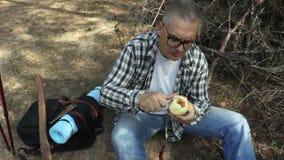 Wanderer isst abgezogenen Apfel stock video footage