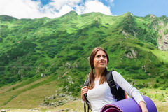 Wanderer junger Dame mit dem Rucksack, der auf Berg sitzt Stockbilder