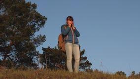 Wanderer-M?dchen, das hei?en Tee trinkt und Sonnenuntergang aufpasst Frauenreisender, steht auf einen trinkenden Kaffee des H?gel stock footage