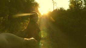 Wanderer-Mädchen mit Rucksack hält Mann eigenhändig und führt ihn Junges Paarhändchenhalten, das auf Landstraße in den Strahlen r stock video footage