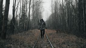 Wanderer man in gas mask walking on old abandoned railway in empty dead forest