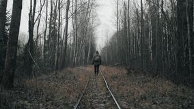 Wanderer in military clothes walking on old railway in empty dead forest