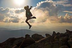Wanderer mit dem Rucksack, der über Felsensonnenunterganghimmel auf dem Hintergrund springt Stockfoto