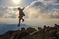 Wanderer mit dem Rucksack, der über Felsensonnenunterganghimmel auf dem Hintergrund springt Lizenzfreie Stockbilder