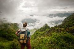 Wanderer mit dem Rucksack, der auf Ansicht des nebeligen Bergs sich entspannt und genießt stockbild