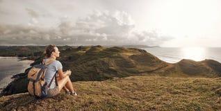 Wanderer mit dem Rucksack, der auf Berg sich entspannt und Wanne genießt lizenzfreies stockbild