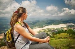 Wanderer mit dem Rucksack, der auf den Berg sich entspannt lizenzfreies stockfoto