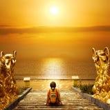 Wanderer mit dem Rucksack, der auf den Schritten sich entspannt und Sonnenuntergang genießt lizenzfreie stockfotografie