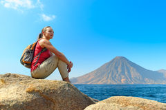 Wanderer mit dem Rucksack, der auf einem Felsen sich entspannt stockfotos