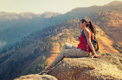 Wanderer mit dem Rucksack, der auf einem Felsen sich entspannt und schönen mou genießt lizenzfreie stockfotografie